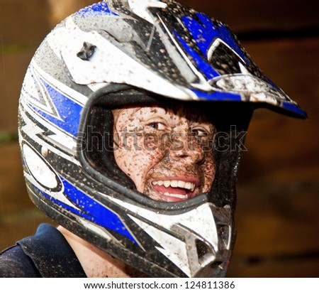 young boy is faszinated by quad driving and enjoyes is, his face is dirty from mud