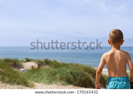 Young boy is having a panoramic view of the entire horizon over water at the North Sea shore in Western Jutland, Denmark. Plenty of copy space.