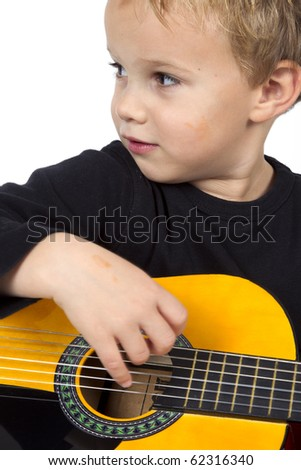Young boy is playing on the guitar on a white background.