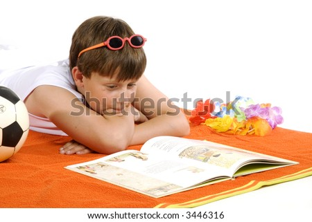 Young boy is relaxing and reading a book