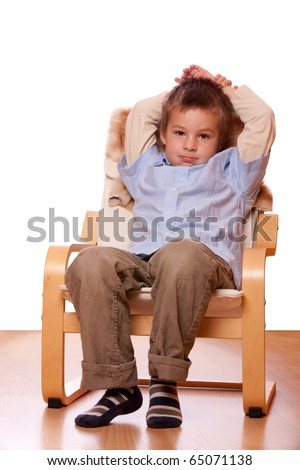 young boy is sitting on a chair