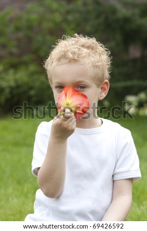 Young boy is trying to figure out what his nose will find.