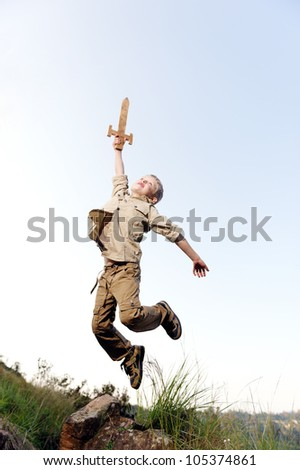 Young boy jumping with wooden sword playing an adventure exploring game outside