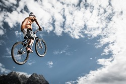 young boy jumps high with his bike in front of mountains and sky