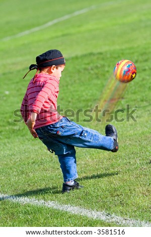 Young boy kicking a ball in the air, having fun in the park. - stock photo