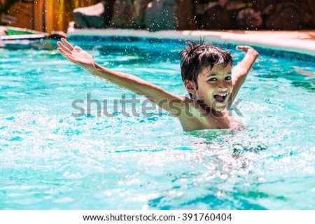 Young boy kid child eight years old splashing in swimming pool having fun leisure activity open arms #391760404