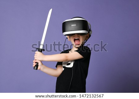 Young boy kid child playing in three-dimensional virtual reality exploring alternative reality in vr glasses fight enemies with katana in hands. Discover future technology