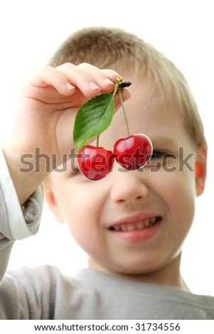 Young boy (kid) holding cherries isolated on white background