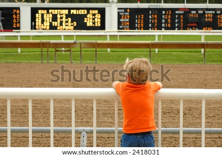 Young boy leaning on railing deep in thought at race track