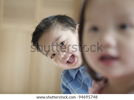 Young boy leaning over his sister's shoulder
