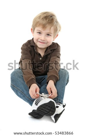 Young boy learning to tie his shoes