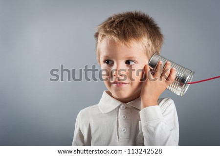 Young boy listen to tin can telephone.