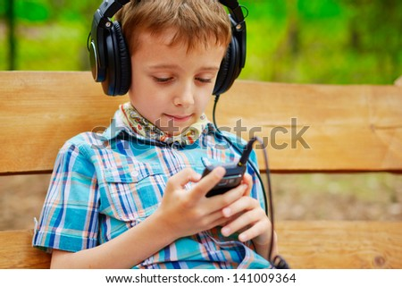 Young boy listening to music on stereo headphones