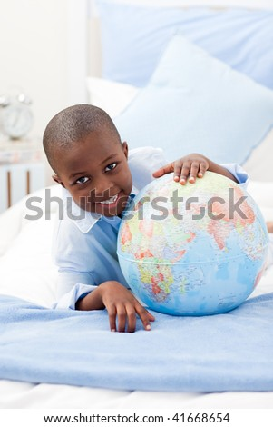 Young Boy looking at a globe while smiling at the camera