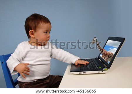 Young boy looking at a laptop with a giraffe sticking its head out through the screen.