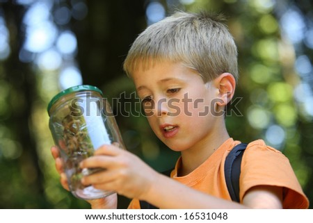 Young boy looking at bug in jar - stock photo