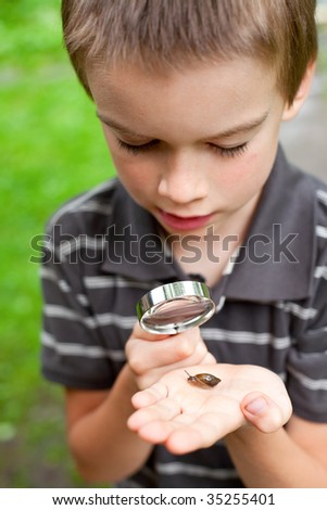 Young boy looking at snail through hand magnifier, focus on snail