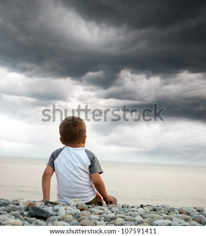 Young boy looking out to sea as storm clouds approach.