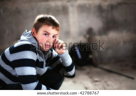 Young boy looking straight against grunge background flash lit 3 light sources