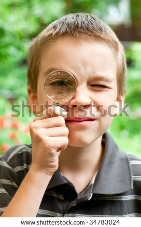 Young boy looking through hand magnifier, shallow DOF