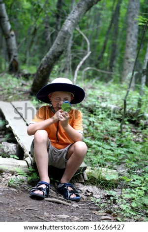 young boy looking through magnifying glass at a leaf found on the hiking  trail