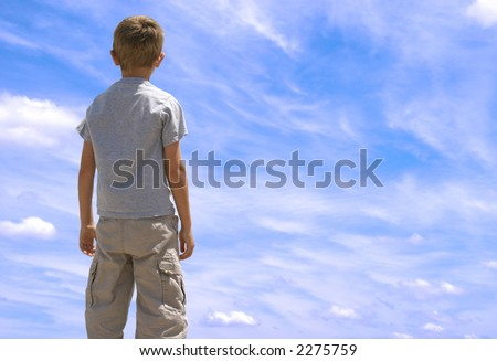 Young boy looking up towards blue sky with clouds.