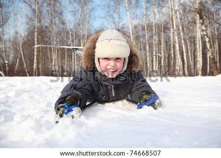 Young boy lying in cross-country skis and poles and smiling inside winter forest at sunny day