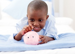 Young Boy lying on his bed putting money into a piggy bank