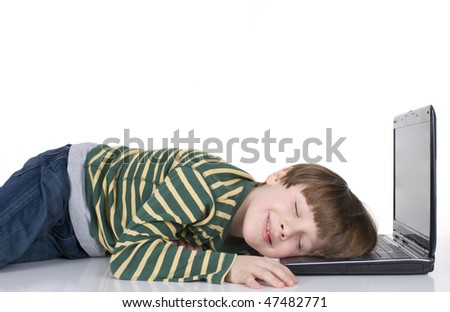 Young boy lying on laptop