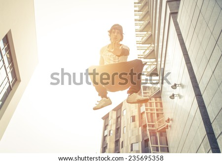 young boy making an high jump while performing parkour