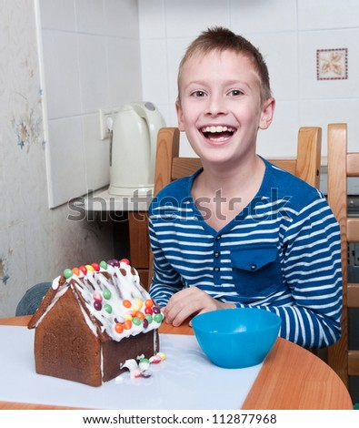 young boy making gingerbread house and laughing
