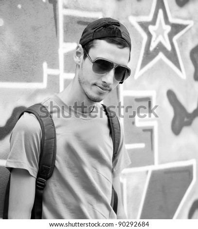 Young boy near graffiti wall. Photo in black and white style.