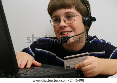 young boy on computer using credit card