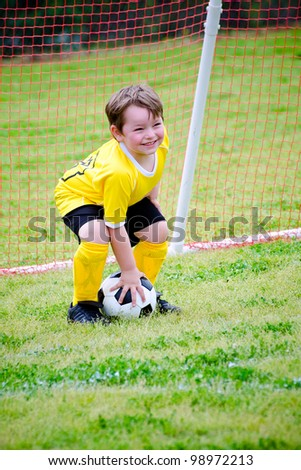 Young boy or kid playing soccer goalie