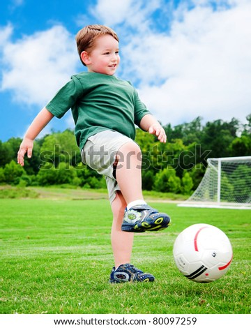 Young boy or kid plays soccer or football sports for exercise and activity.
