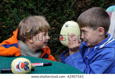 young boy painting halloween pumpkin with a smiling face