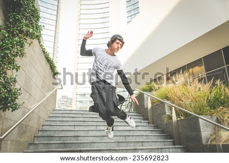 young boy performing parkour movement in the city center