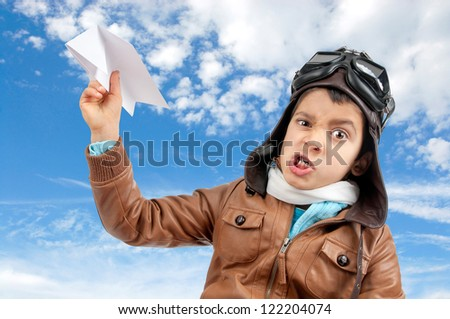 Young boy pilot flying a paper plane