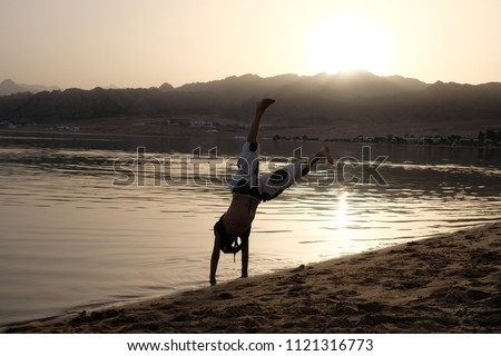 Young boy play capoeira at the Dahab beach. Child is happy and have fun to make sports near the sea during sunset. Best summer vacation upside down. Silhouette of biy making acrobatic tricks. Freedom.