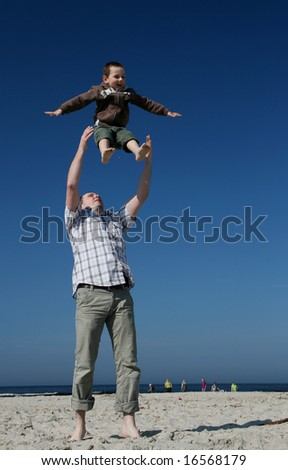 Young boy play with father. Father throwing his son into the air.