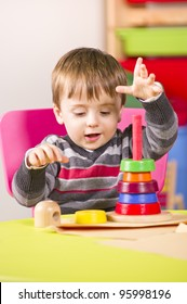 A stock photo of a young boy playing with stacking blocks in a nursery room
