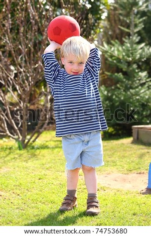 Young boy playing ball in the garden