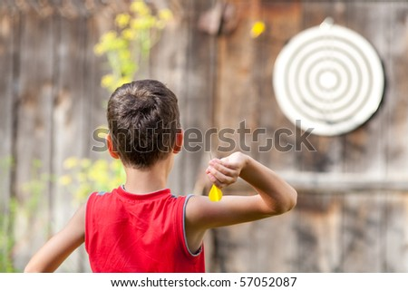 Young boy playing darts outdoor - stock photo