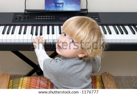 Young boy playing electric piano or keyboard and looking at the camera