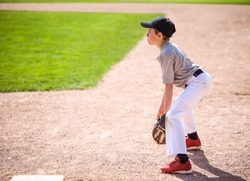 Young boy playing first base in a baseball game, shallow focus on arm and glove