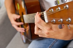 Young boy playing guitar. Close-up of man hand playing classic guitar. teenager learning playing guitar.