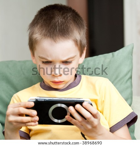 Young boy playing handheld game console