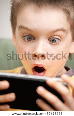 Young boy playing handheld game console #57695296