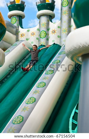 Young boy playing in inflatable playground