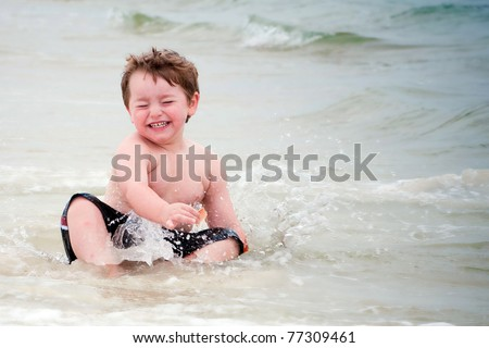 Young boy playing in surf at beach.